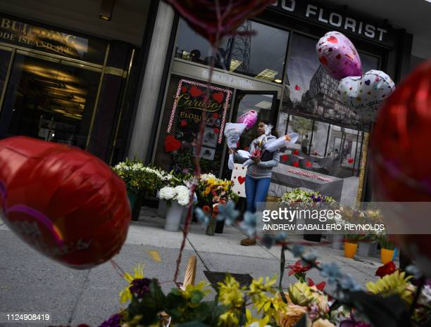A woman walks out of Caruso Florist with a bouquet of flowers on Valentines Day in Washington DC on February 14 2019