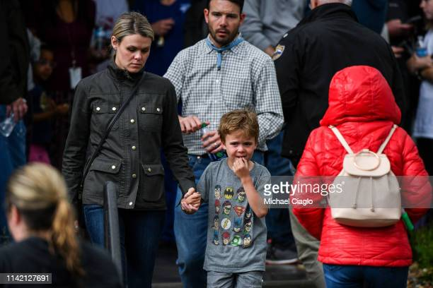 A woman walks out of the Recreation Center at Northridge with her son after at least seven students were injured during a shooting at STEM School...