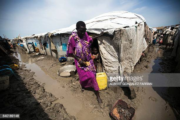 TOPSHOT A woman walks outside her shelter in the Protection of Civilians site in Malakal on June 14 2016 The rainy season started and made the living...