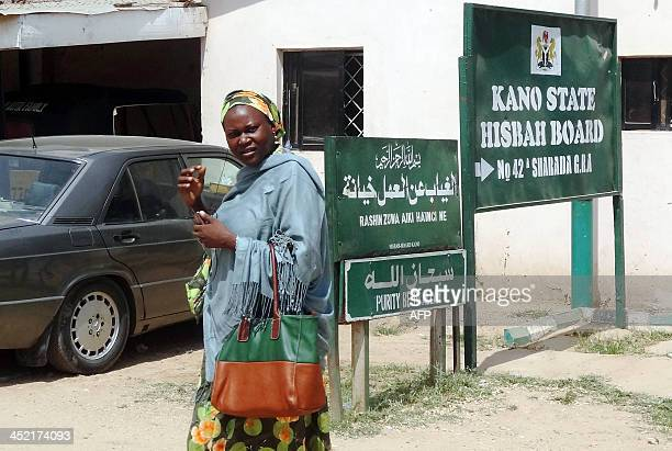 A woman walks outside the office for sharia enforcement agency called Hisbah Board in the northern Nigerian city of Kano on October 28 2013The Hisbah...