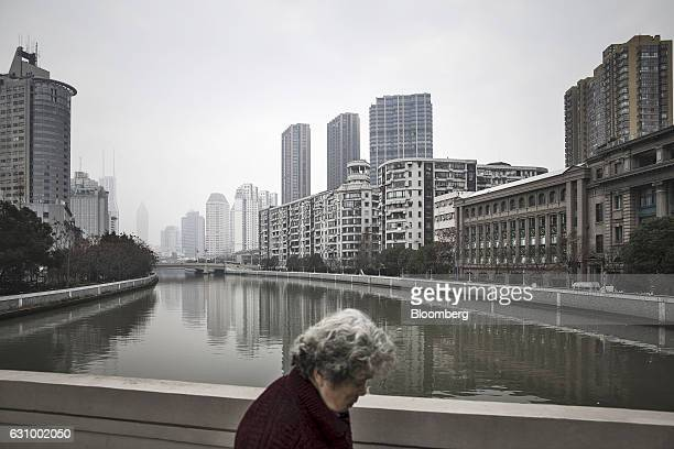 A woman walks over a bridge overlooking Suzhou Creek in Shanghai China on Wednesday Jan 4 2017 After defying skeptics with solid growth last year...