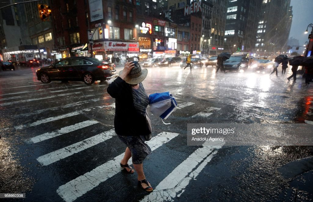 A woman walks over a pedestrian crossing with her umbrella on a rainy day in New York, United States on May 15, 2018.