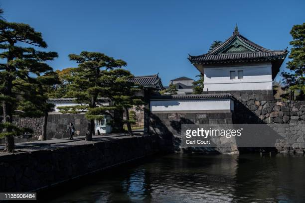 A woman walks over a walkway leading from Kikyomon Gate in the Imperial Palace on April 9 2019 in Tokyo Japan Tokyo's Imperial Palace was built on...
