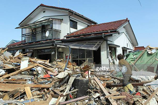 A woman walks over debris piled up as she returns to her home in the city of Natori in Miyagi prefecture on March 13 2011 two days after the area was...