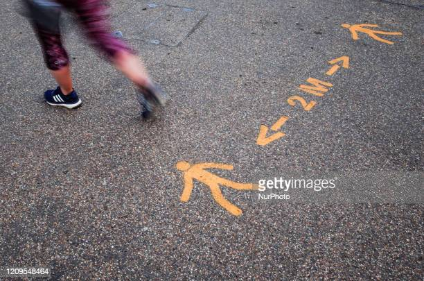 Woman walks over markings reminding people to remain two metres apart, recommended by the government for successful 'social distancing', on...