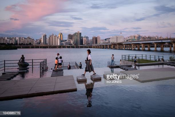 TOPSHOT A woman walks over steppingstones before the Han river and Seoul's skyline at Yeouido park on September 26 2018 South Korea is observing the...