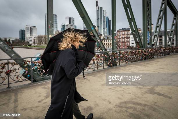 A woman walks over the bridge 'Eiserner Steg' during high winds from storm Sabine on February 10 2020 in Frankfurt Germany The storm called Ciara in...