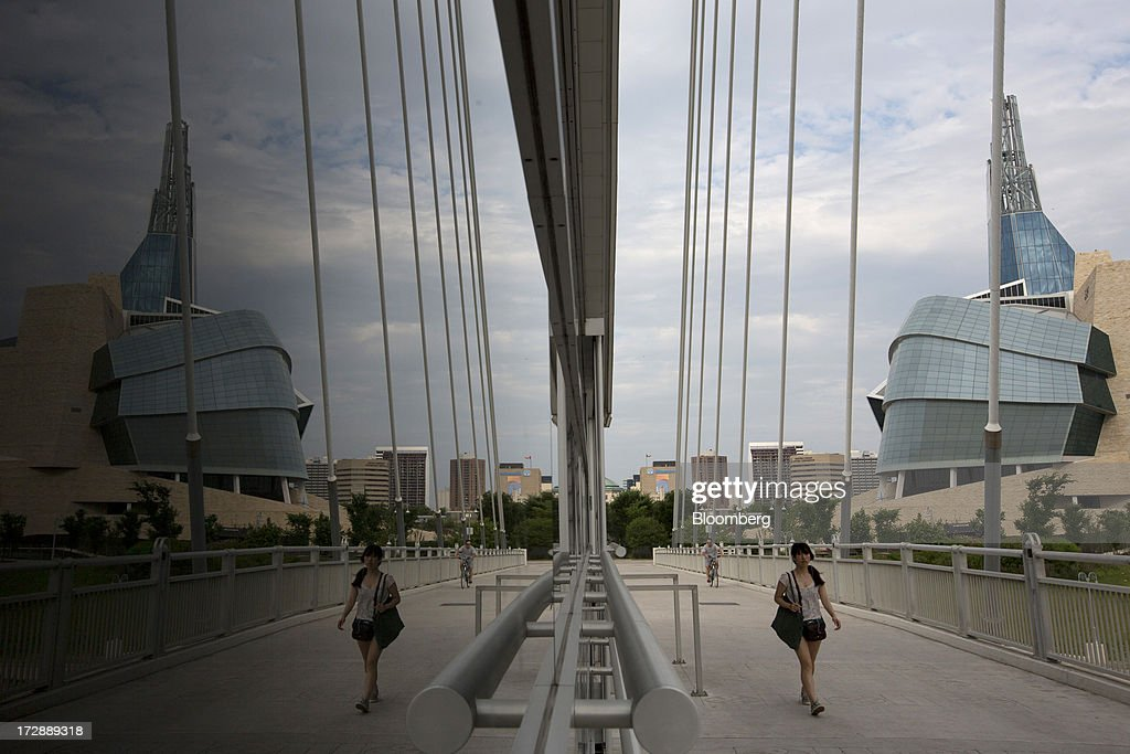 A woman walks over the Provencher Bridge in Winnipeg, Manitoba, Canada, on Thursday, July 4, 2013. Canada extended the longest streak of merchandise trade deficits in a quarter century in May, with the shortfall narrowing as imports fell faster than exports. Photographer: Brent Lewin/Bloomberg via Getty Images