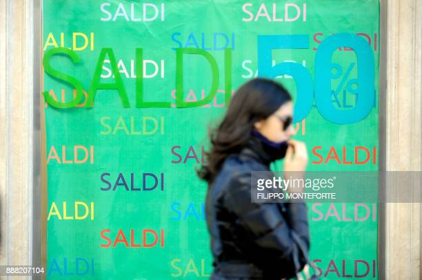A woman walks passed a shopwindow near Via Condotti one of central Rome's main shopping streets for the second day of sales on January 3 2010...