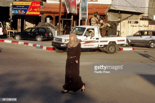 Woman walks passed Palestinian militants from Izz al-Din al-Qassam Brigades, of Hamas during the marking of Nakba or the ''Day of Catastrophe'' in...