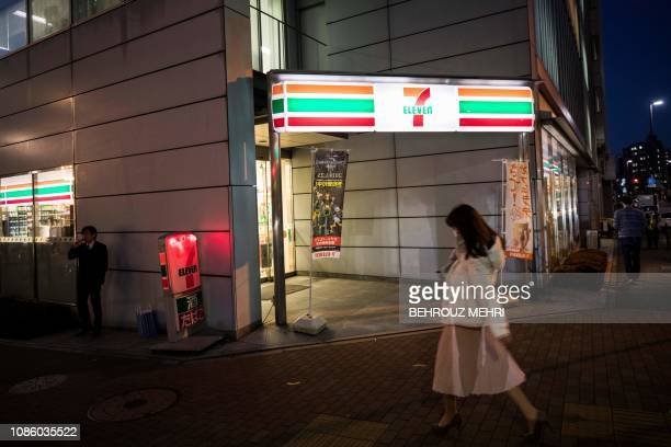 A woman walks past a 7Eleven convenience store in Tokyo on January 22 2019 Japan's omnipresent convenience stores are preparing to stop selling...
