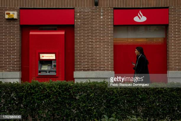 Woman walks past a Banco Santander's branch before a news conference to announce the 2019 results on January 29, 2020 in Boadilla del Monte, in...