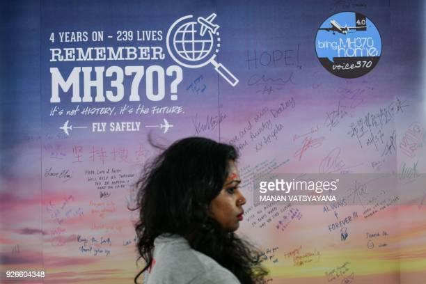 A woman walks past a banner bearing solidarity messages for passengers of the missing Malaysia Airlines flight MH370 during a memorial event in Kuala...