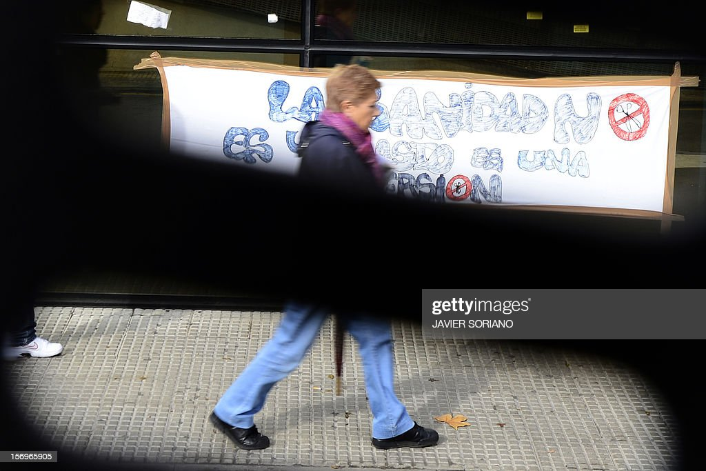 A woman walks past a banner outside the Hospital Clinico San Carlos in Madrid where Spanish doctors, nurses and hospital staff denounce budget cuts and privatisations on November 26, 2012. The health sector has been hard hit by the austerity policies implemented by the rightwing government of Mariano Rajoy, which is trying to cut the public deficit in the eurozone's fourth largest economy.