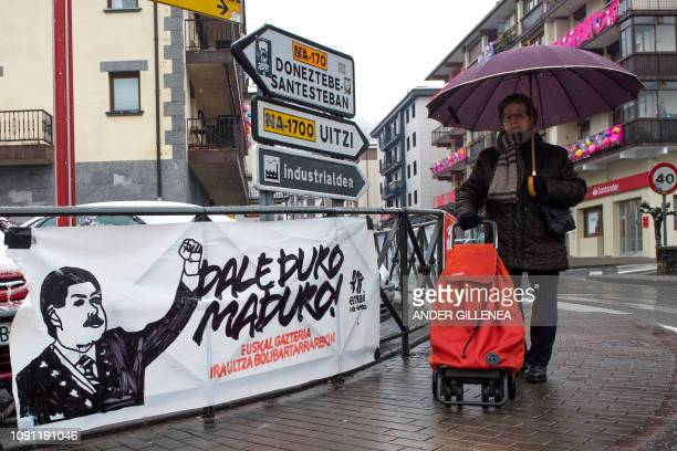 A woman walks past a banner reading 'Be hard Maduro the Basque youth is with the Bolivarian revolution' in support of Venezuelan President Nicolas...