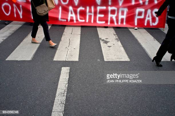 A woman walks past a banner reading 'We will not give up' during a demonstration in Lyon central eastern France on October 11 during a national day...