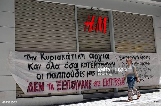 A woman walks past a banner taped to the front of a Hennes Mauritz AB fashion clothing store that demonstrates against stores opening and trading on...