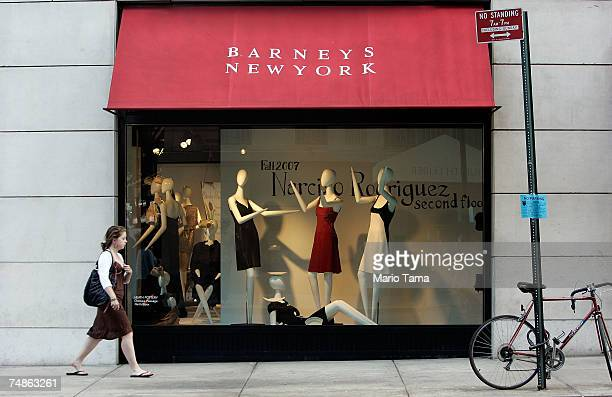 A woman walks past a Barneys New York store window June 22 2007 in New York City Jones Apparel Group Inc plans to sell Barneys New York to the Dubai...