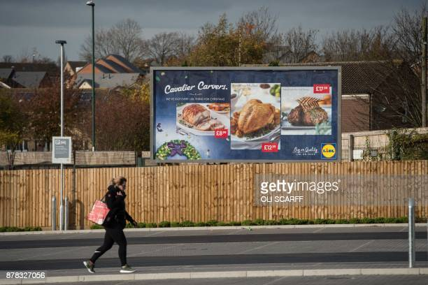 A woman walks past a billboard advertisement for Christmas food outside a branch of the discount supermarket Lidl in Nottingham central England on...