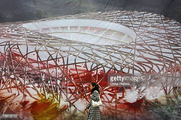 A woman walks past a billboard featuring National Stadium structure dubbed the 'Bird's Nest' on March 14 2007 in Beijing China Tickets for the 2008...