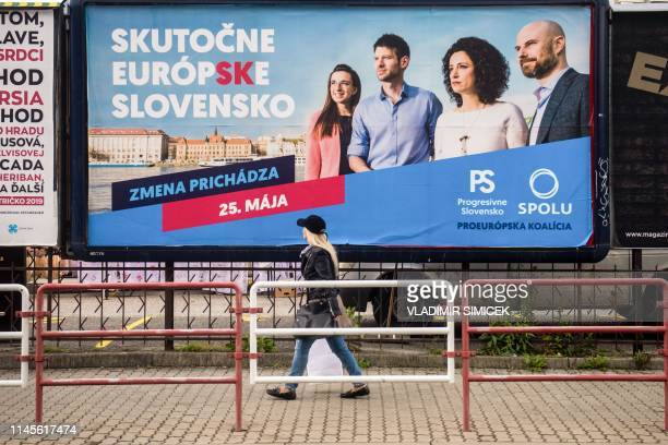 A woman walks past a billboard of candidates for the European Parliament elections of the parties Progresivne Slovensko and Spolu reading Really...
