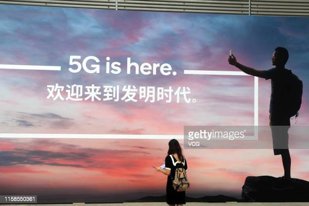Woman walks past a billboard reading '5G is here' on day one of the Mobile World Congress Shanghai 2019 at the Shanghai New International Expo Center...