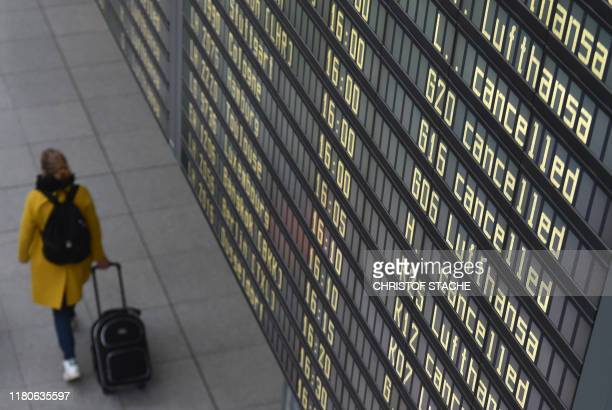 """Woman walks past a board displaying cancelled flights of German airline Lufthansa at the """"Franz Josef Strauss"""" airport in Munich, southern Germany,..."""