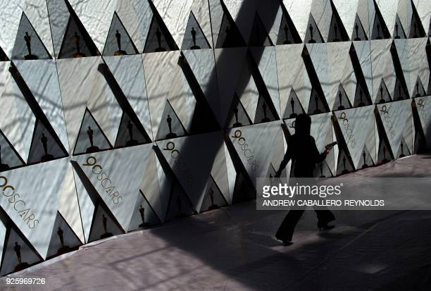 A woman walks past a board on the red carpet during preparations for the 90th annual Academy Awards week in Hollywood California on March 1 2018 /...