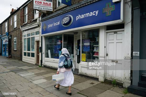 A woman walks past a Boots pharmacy on July 09 2020 in York United Kingdom Many UK businesses are announcing job losses due to the effects of the...