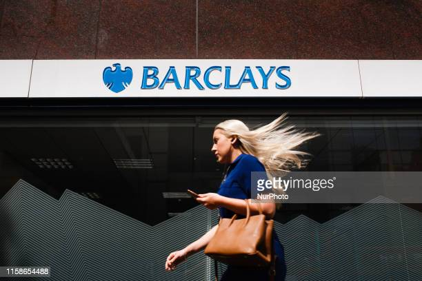 A woman walks past a branch of Barclays bank on Wormwood Street in London England on July 26 2019 Four major UK banks including Barclays are set to...