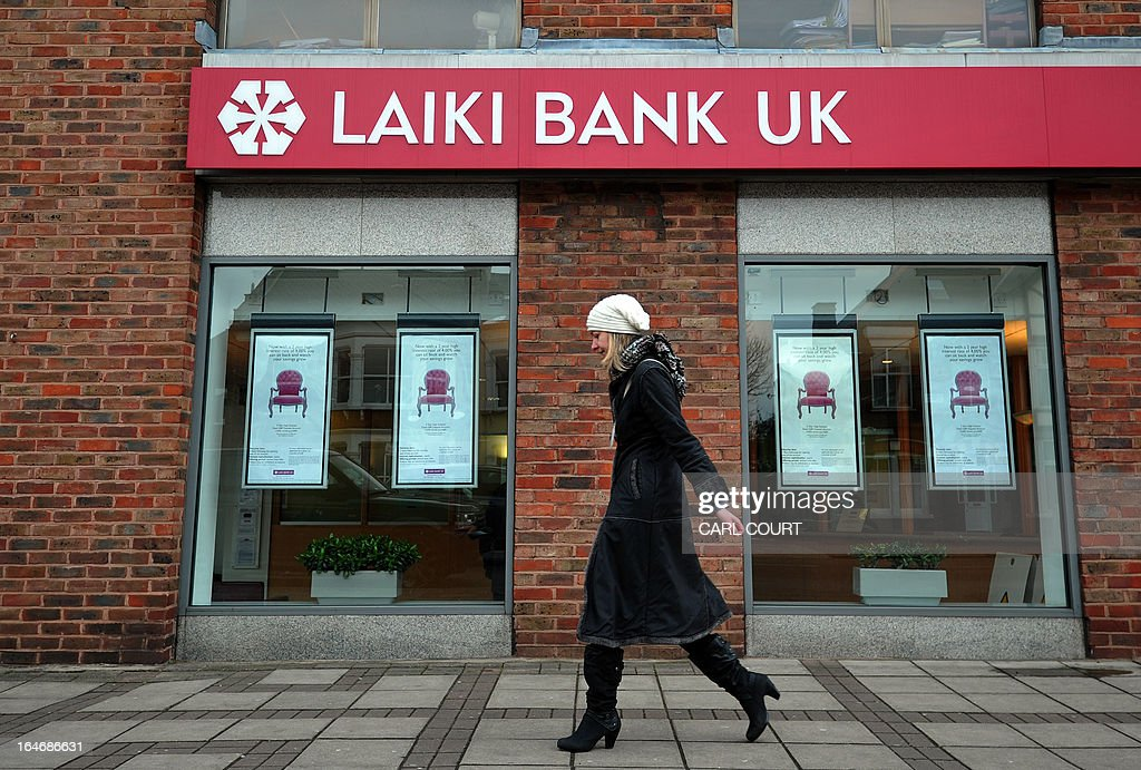 A woman walks past a branch of Laiki Bank UK, a subsiduary of Cyprus Popular Bank (Laiki Bank), in north London on March 26, 2013. British Chancellor of the Exchequer George Osborne revealed the government was in negotiation with Cyprus to find a solution regarding branches of Cyprus Popular Bank (Laiki Bank) in Britain. Cyprus's second largest bank Laiki will wind up in Cyprus under a painful restructuring plan that was a condition of the eurozone bailout.