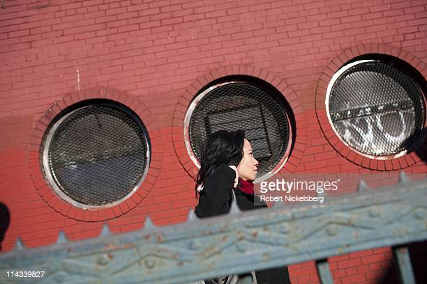 Woman walks past a brick building near the Prospect Avenue subway station March 29, 2011 in Brooklyn, New York. In 2009, the New York City Subway...