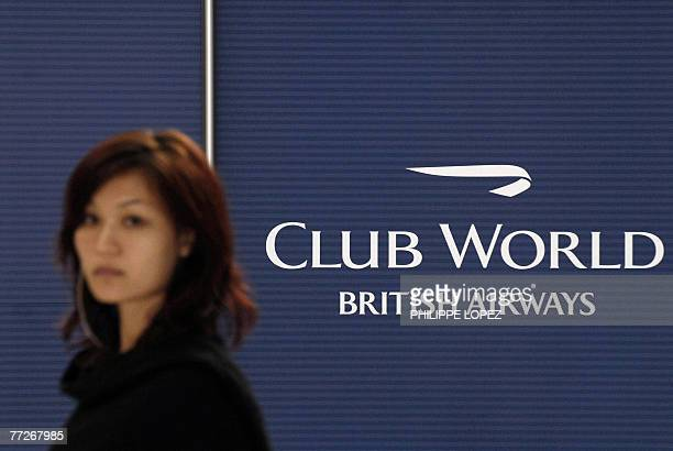 A woman walks past a British Airways logo of the 'Club World' cabin during its unveiling in Hong Kong 11 October 2007 The cabin is available in...