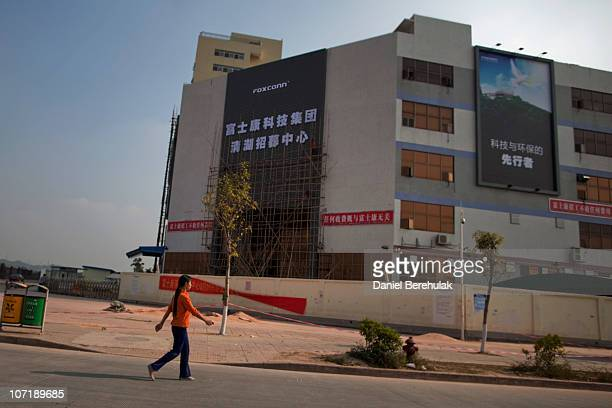 A woman walks past a building owned by the contract manufacturer Foxconn International Holdings Ltd on November 28 2010 in Shenzhen China According...