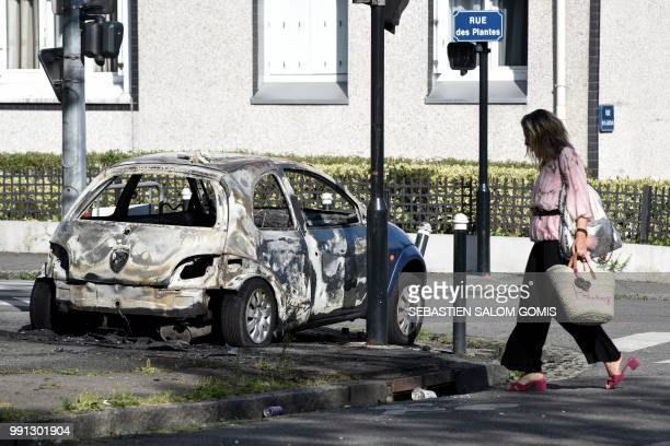 A woman walks past a burned car on July 4 2018 in the Breil neighborhood of Nantes following clashes between groups of young people and police in the...