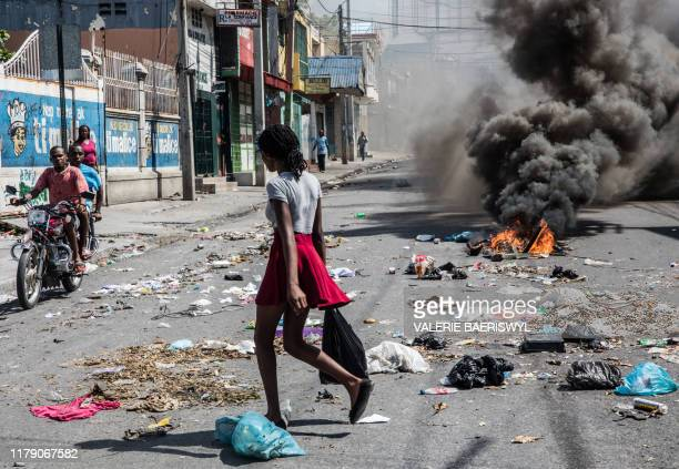 Woman walks past a burning trash during a demonstration demanding the resignation of President Jovenel Moise in the Haitian capital in Port-au-Prince...