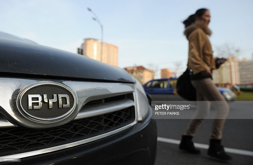 A woman walks past a BYD car on a street in Shanghai on March 25, 2013. Chinese electric car producer BYD, which is partly backed by US investment titan Warren Buffett, said its net profit plunged more than 94 percent year-on-year in 2012, hit by slowing growth in the country. AFP PHOTO/Peter PARKS
