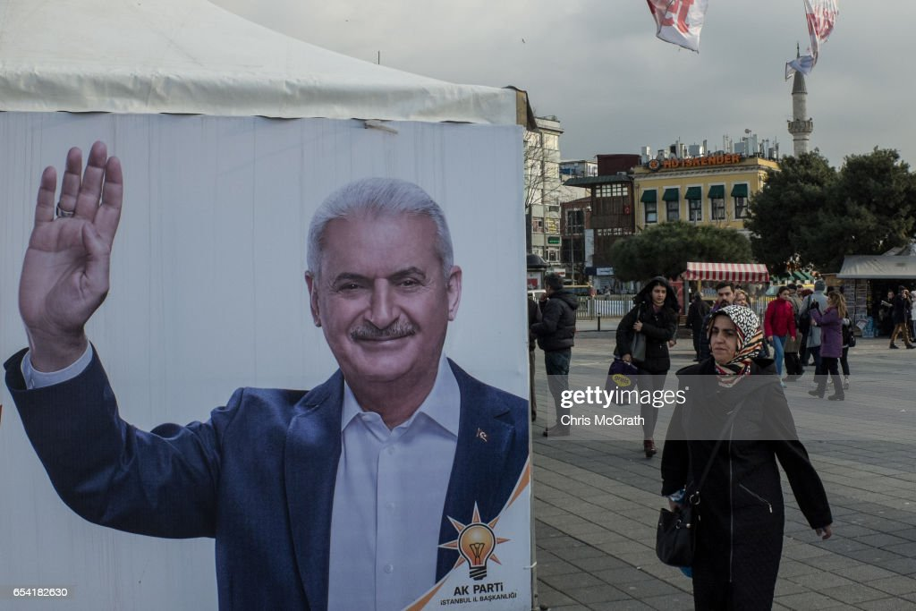 A woman walks past a campaign booth showing a portrait of Turkish Prime Minister Binali Yildirim supporting the 'Yes'(EVET) vote on March 16, 2017 in Istanbul, Turkey. Turkey will hold its constitutional referendum on April 16, 2017. Turks will vote on 18 proposed amendments to the Constitution of Turkey. The controversial changes seek to replace the parliamentary system and move to a presidential system which would give President Recep Tayyip Erdogan executive authority.