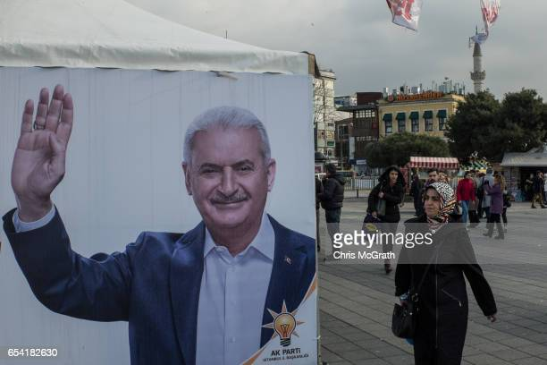 """Woman walks past a campaign booth showing a portrait of Turkish Prime Minister Binali Yildirim supporting the """"Yes"""" vote on March 16, 2017 in..."""