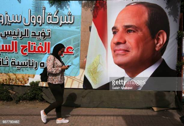 A woman walks past a campaign sign for Egyptian President Abdel Fattah alSisi one day before the presidential elections on March 25 2018 in Cairo...