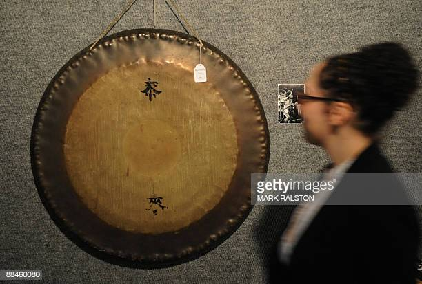 A woman walks past a Chinese gong used by the drummer John Bonham from Led Zeppelin during a preview for an upcoming auction in Los Angeles on June...