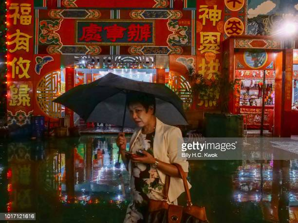 A woman walks past a Chinese opera house during the month of Hungry Ghost Festival on August 10 2018 in Hong Kong The Yu Lan Festival one of China's...