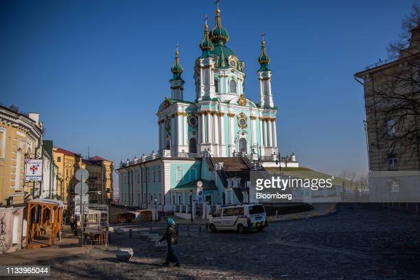 A woman walks past a church in the early morning in Kiev Ukraine on Sunday March 31 2019 Ukrainians will choose between a field of almost 40...