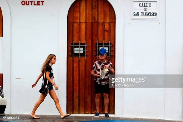 A woman walks past a closed down business as a man looks on in San Juan Puerto Rico on November 7 2017 The Center for Puerto Rican Studies at Hunter...
