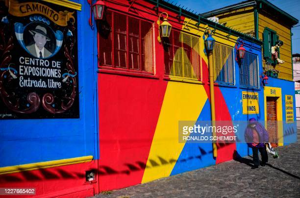 A woman walks past a closed restaurant at La Boca neighbourhood in Buenos Aires on July 14 2020 amid the new coronavirus pandemic Buenos Aires' La...