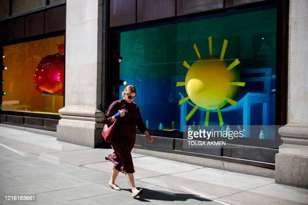 A woman walks past a closed Selfridges department store on Oxford Street in central London's main high street retail shopping area on May 29 2020...