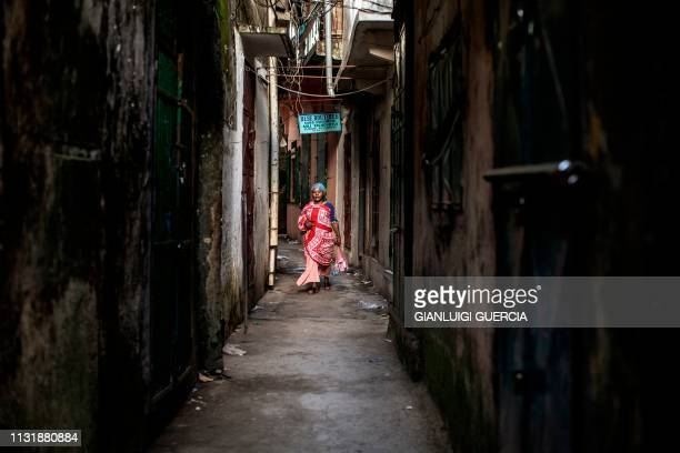 TOPSHOT A woman walks past a closed shop on an alleyway in the medina of Mutsamudu the capital of Anjouan Island Comoros on March 21 2019 People of...