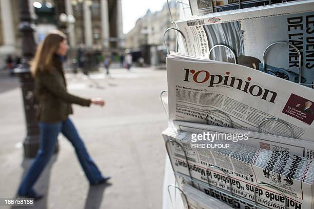 A woman walks past a copy of the newspaper 'L'opinion' on sale in a newsstand on May 15 2013 in Paris The newspaper also available online was...