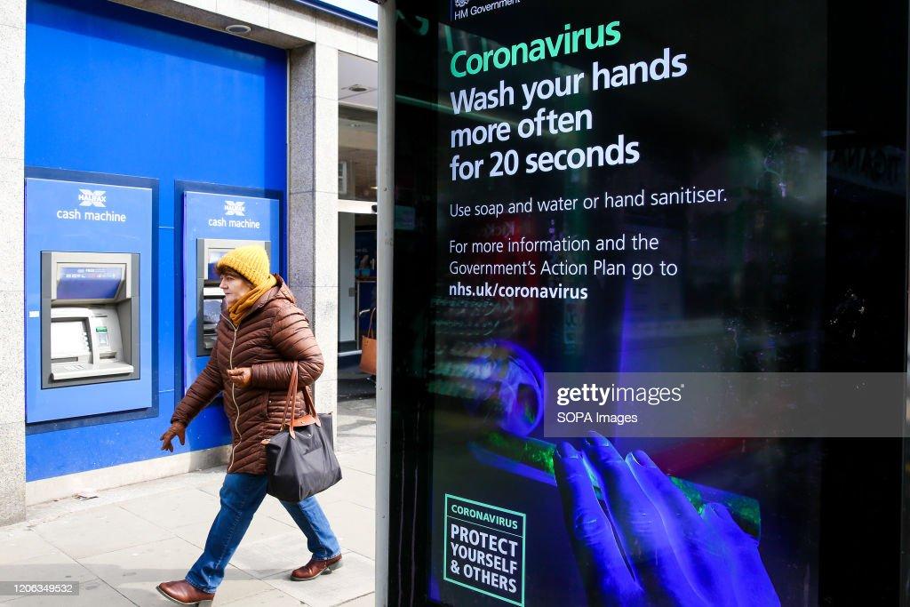 A woman walks past a Coronavirus public information campaign... : News Photo