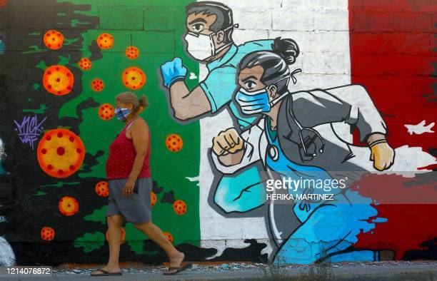 Woman walks past a coronavirus-related mural painted by artist Mick Martinez in Ciudad Juarez, state of Chihuahua, Mexico, on May 19, 2020.